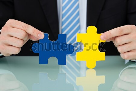Businessman Joining Puzzle Pieces Stock photo © AndreyPopov