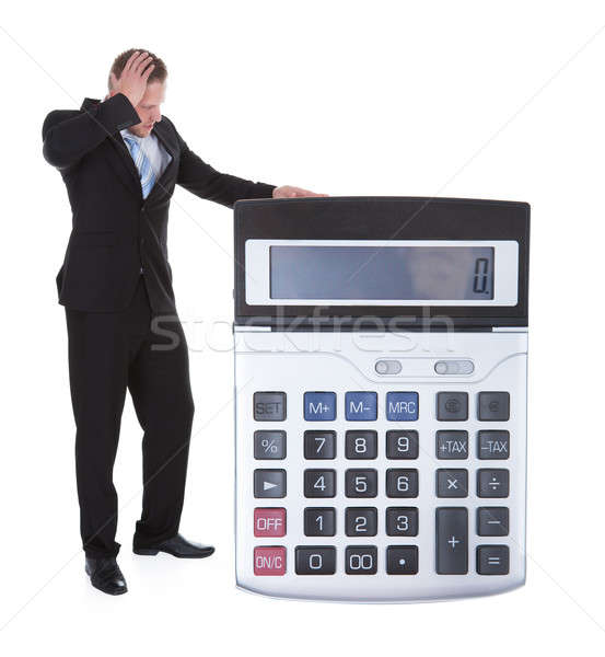 Worried businessman viewing a large calculator Stock photo © AndreyPopov