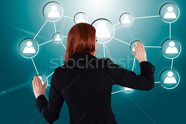 Businesswoman Touching Connected Human Icons Stock photo © AndreyPopov