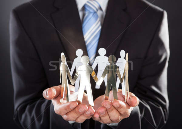 Stock photo: Businessman Holding Metal Team In Cupped Hands