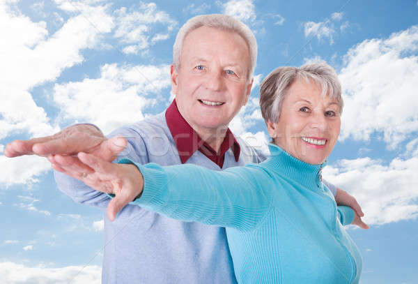 Senior Couple With Arms Outstretched Standing Against Cloudy Sky Stock photo © AndreyPopov