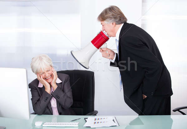Man Yelling With Megaphone On Woman Stock photo © AndreyPopov