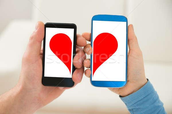 Couple Holding Cellphone With Half Heart Symbol Stock Photo Andriy