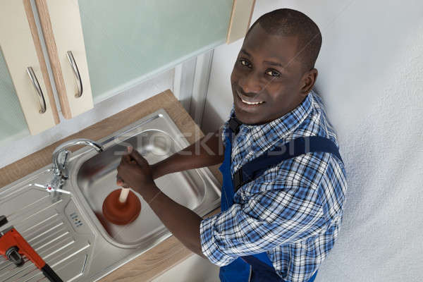 Plumber Using Plunger In Kitchen Sink Stock photo © AndreyPopov