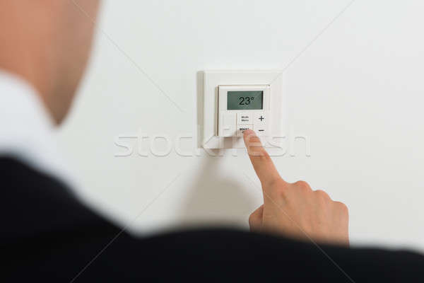 Businessperson Setting Temperature On Digital Thermostat Stock photo © AndreyPopov