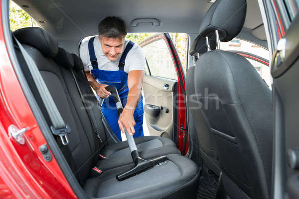 Handyman Vacuuming Car Back Seat With Vacuum Cleaner Stock photo © AndreyPopov