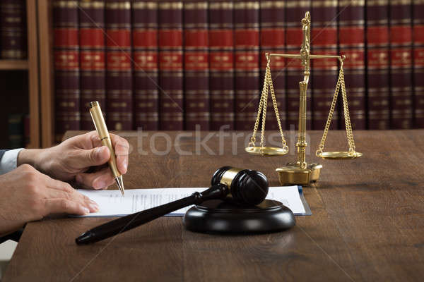 Judge Writing On Legal Documents At Desk Stock photo © AndreyPopov