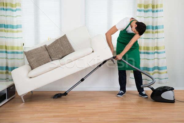 Férfi emel kanapé takarítás padló porszívó Stock fotó © AndreyPopov
