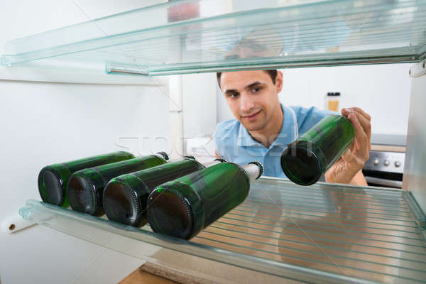 Smiling Man Removing Beer Bottle From Refrigerator Stock photo © AndreyPopov