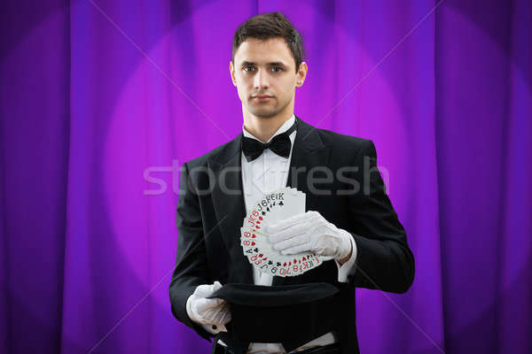 Magician Putting Playing Cards In Hat Stock photo © AndreyPopov