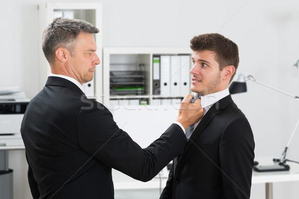 érett üzletember lebilincselő alkalmazottak nyakkendő oldalnézet Stock fotó © AndreyPopov