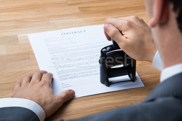 Businessman Stamping Contract Document At Desk Stock photo © AndreyPopov