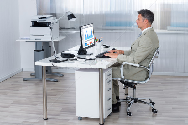Businessman Using Computer At Desk In Office Stock photo © AndreyPopov