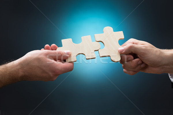 Closeup Of Businessmen Joining Jigsaw Pieces Stock photo © AndreyPopov