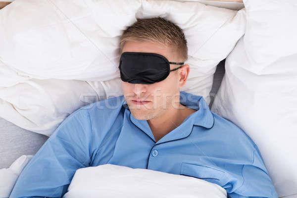 Man Sleeping On Bed Wearing Eyemask Stock photo © AndreyPopov