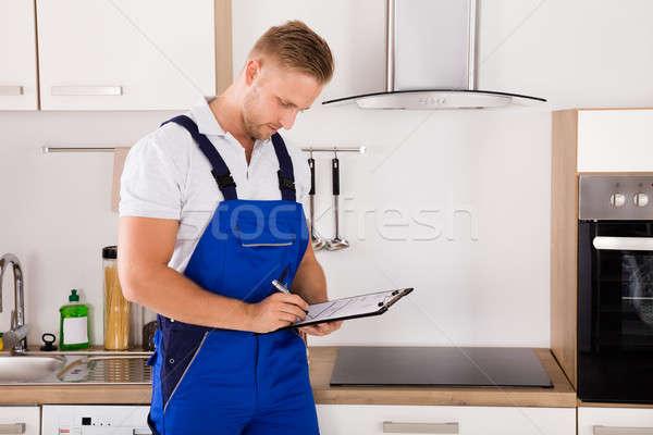Repairman Writing On Clipboard Stock photo © AndreyPopov