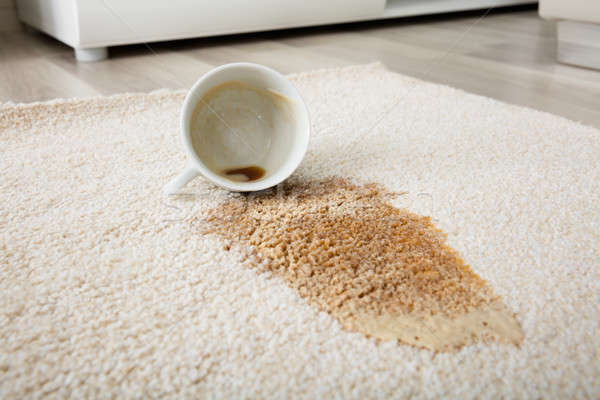 Stock photo: Coffee Spilling From Cup On Carpet