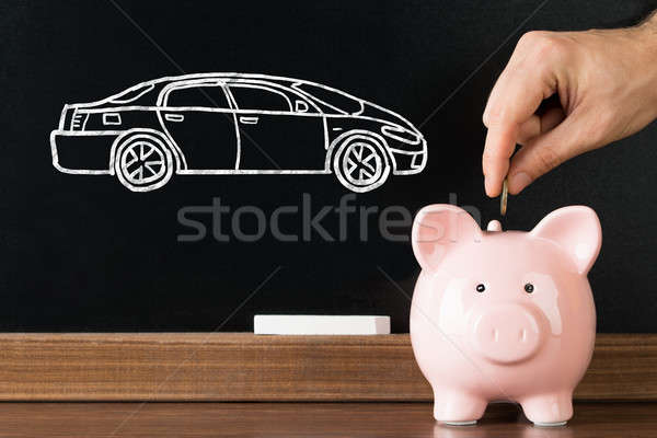 Person Inserting Coin In Piggybank For Purchasing New Car Stock photo © AndreyPopov