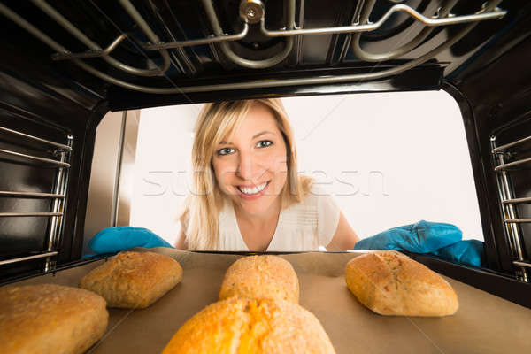 Woman Inserting Cookies Tray In Oven Stock photo © AndreyPopov