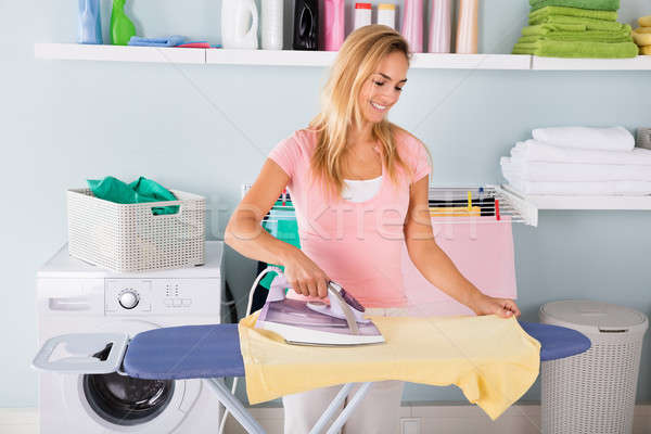 Smiling Woman Ironing T-shirt On Ironing Board Stock photo © AndreyPopov