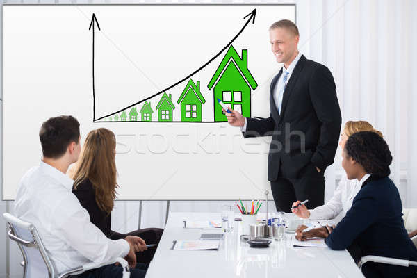 Businessman Giving Presentation On House Rising Concept Stock photo © AndreyPopov