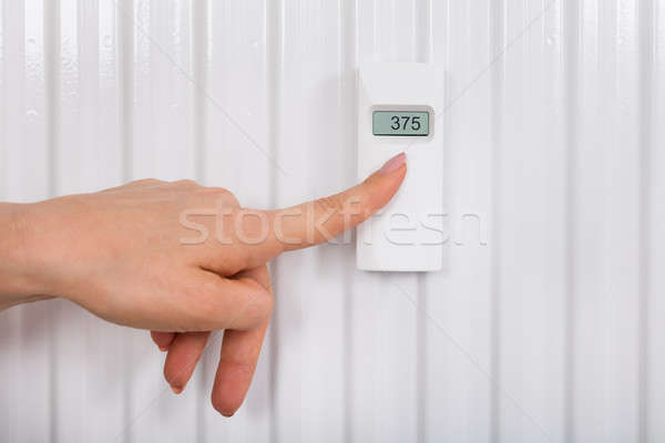 Person Adjusting Temperature With Digital Thermostat Stock photo © AndreyPopov