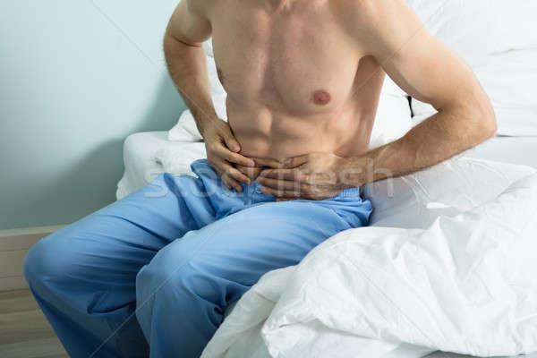 Mann Leiden Magenschmerzen Sitzung Bett home Stock foto © AndreyPopov