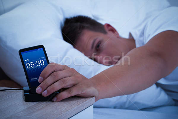 Man Waking Up With Mobile Alarm Clock Stock photo © AndreyPopov