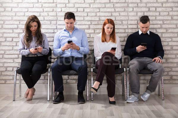 Richiedente cellulare uomini d'affari seduta sedia Foto d'archivio © AndreyPopov