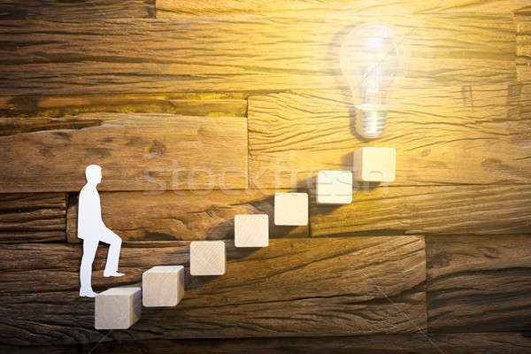 бизнесмен скалолазания лестнице ведущий лампочка Сток-фото © AndreyPopov