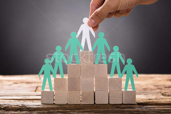 Stock photo: Hand Placing Paper Businessman With Employees On Pyramid Blocks