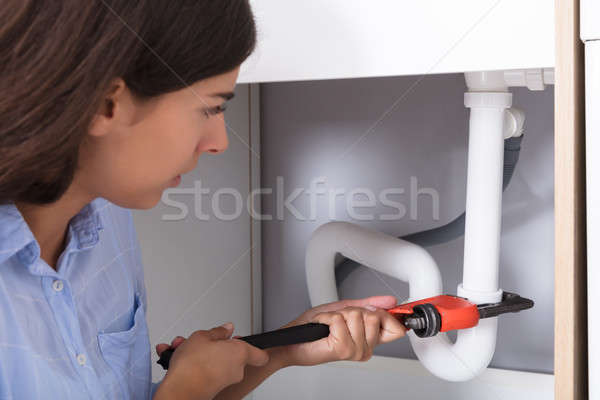 Young Woman Tightening Sink Pipe With Monkey Wrench Stock photo © AndreyPopov