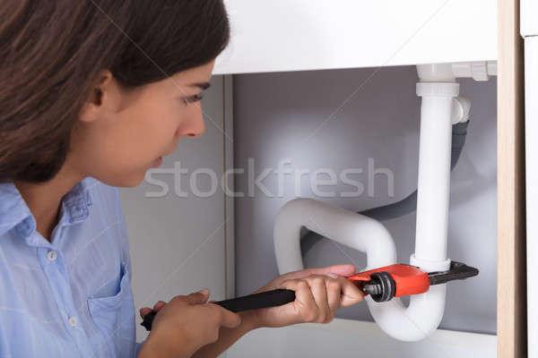 Jonge vrouw wastafel pijp aap sleutel Stockfoto © AndreyPopov