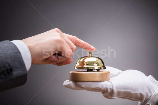 Person Ringing Service Bell Held By Waiter Stock photo © AndreyPopov