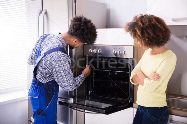 Repairman Fixing Oven In Kitchen Stock photo © AndreyPopov