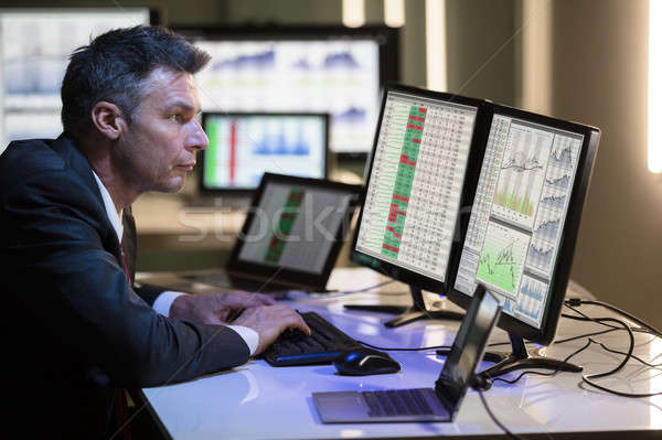 Stock Market Broker Analyzing Graph On Multiple Computer Screen Stock photo © AndreyPopov
