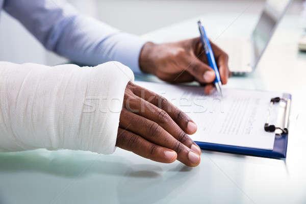 Injured Man Filling Insurance Claim Form Stock photo © AndreyPopov