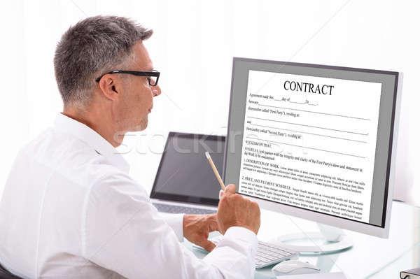 üzletember olvas szerződés számítógép érett munkahely Stock fotó © AndreyPopov