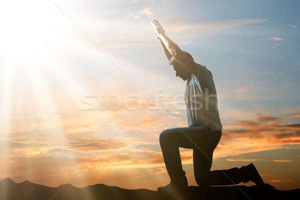 Férfi térdel imádkozik naplemente oldalnézet felhős Stock fotó © AndreyPopov