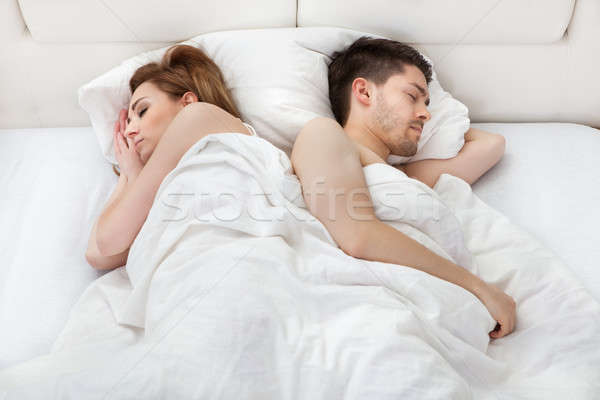 Young couple sleeping on bed Stock photo © AndreyPopov