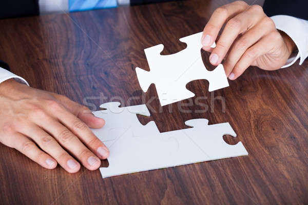 Close-up Of Businessman Completing Jigsaw Puzzle Stock photo © AndreyPopov