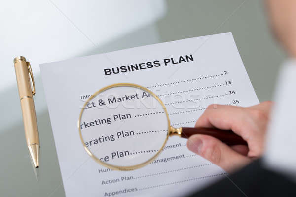 Businessman Examining Business Plan With Magnifying Glass Stock photo © AndreyPopov