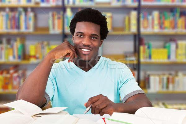 Férfi egyetemi hallgató tanul könyvtár portré mosolyog Stock fotó © AndreyPopov