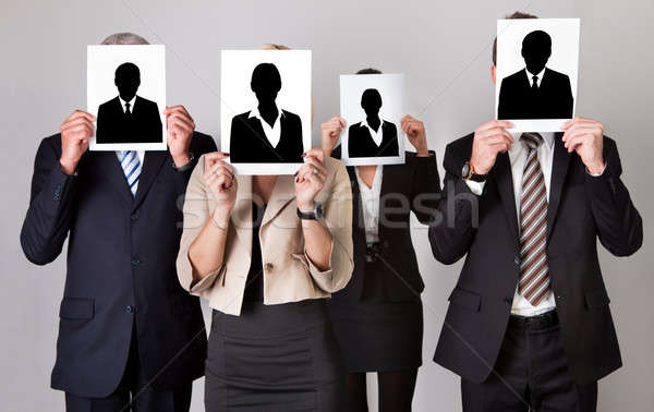 Businesspeople Holding Photographs In Front Of Faces Stock photo © AndreyPopov