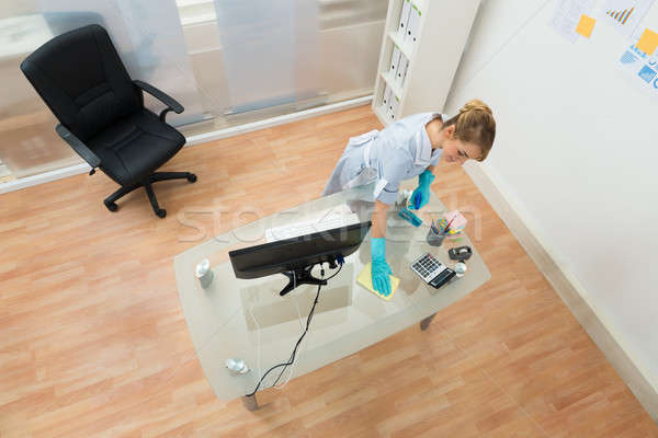 Young Maid Cleaning Desk Stock photo © AndreyPopov
