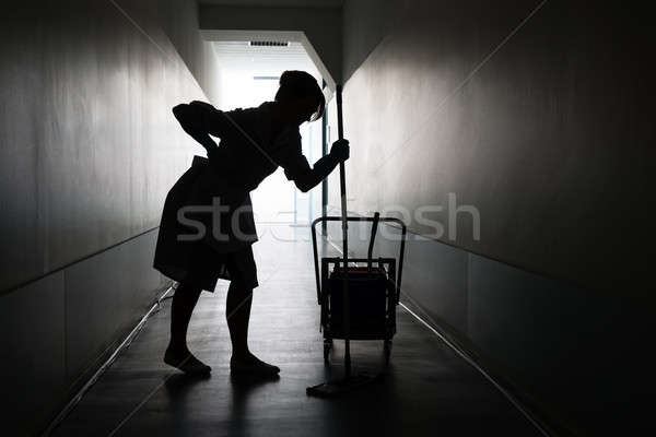 Silhouette Of Maid Suffering From Backache Stock photo © AndreyPopov