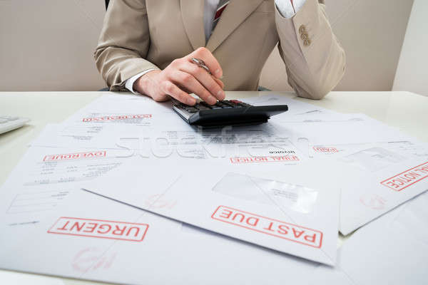 Businessman With Calculator And Unpaid Bills Stock photo © AndreyPopov