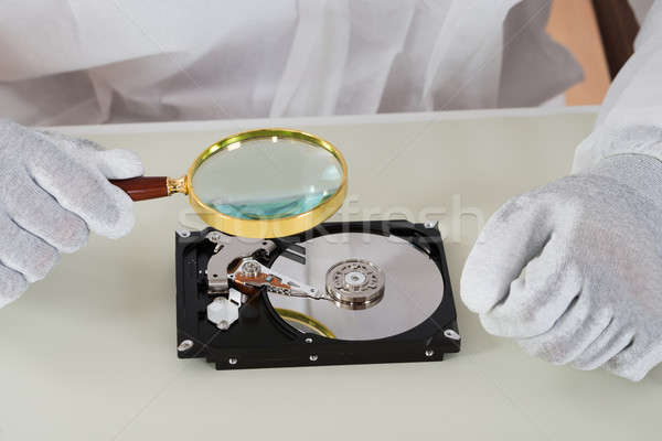 Person Holding Magnifying Glass Over Harddisk Stock photo © AndreyPopov