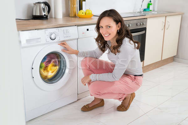Woman Cleaning Clothes In Washing Machine Stock photo © AndreyPopov