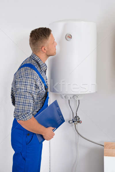 Repairman Looking At Dial Gauge On Electric Boiler Stock photo © AndreyPopov